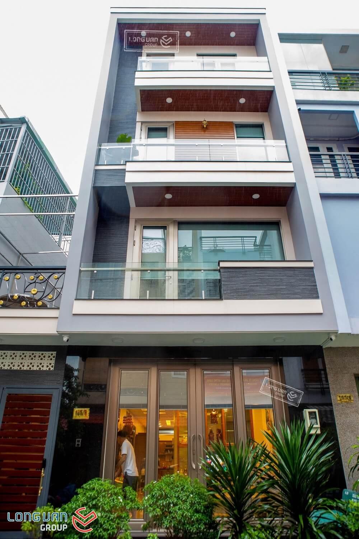 Tone màu trầm ấm của ngôi nhà kết hợp với hệ cửa lớn màu kim loại Anode tạo thành điểm nhấn hút mắt và độc đáo.